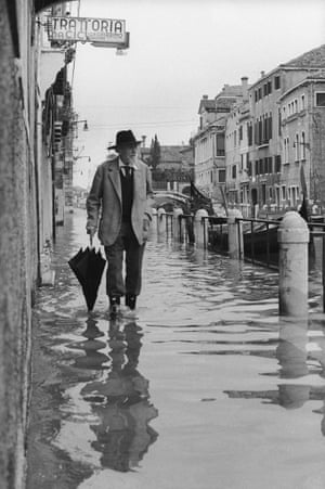 "March 1964: Poet Ezra Pound walks along a flooded pavement. Excessive groundwater pumping in the 20th century, combined with rising sea-levels in the lagoon has led to the city ""sinking"" at an average of 2mm each year."