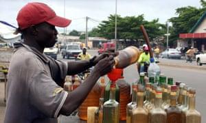 A trader bottles smuggled fuel on a street of Benin's capital Cotonou