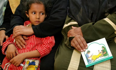 A woman holds a card in her lap about the problems with female genital mutilation (FGM) during a session to educate women in Minia, Egyp
