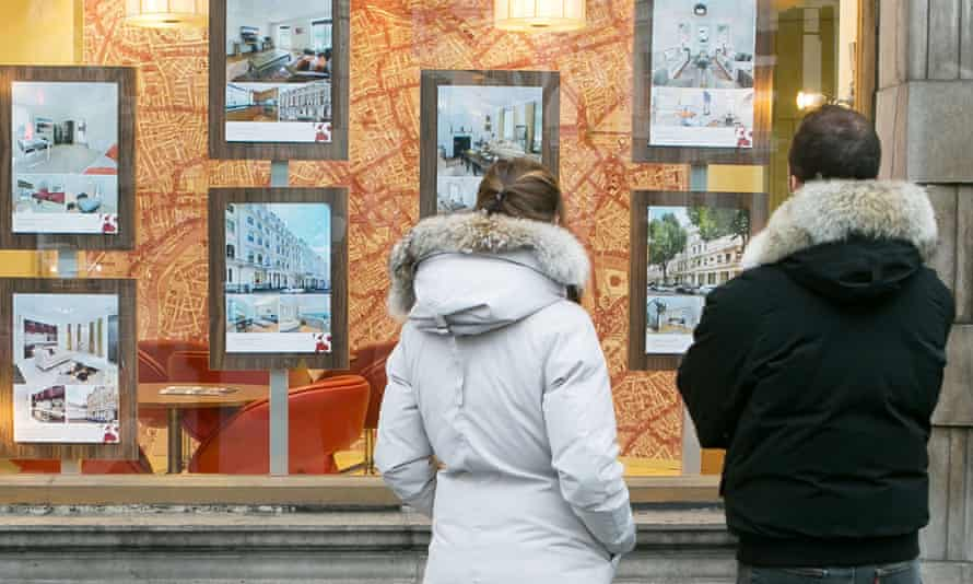 Young people looking in an estate agent's window