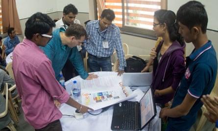 Participants at a Kumbathon workshop talk MIT's John Werner through their idea