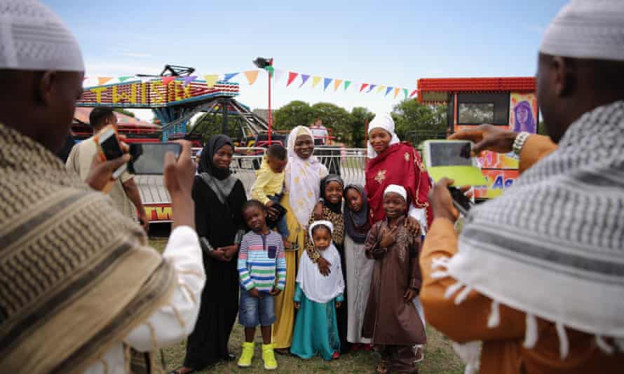 A family has their photograph taken after morning prayers during an Eid celebration in Burgess Park, south London.