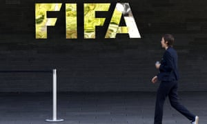 Staff walks past a logo of soccer's international governing body FIFA at their headquarters in Zurich, Switzerland, 27 May 2015.