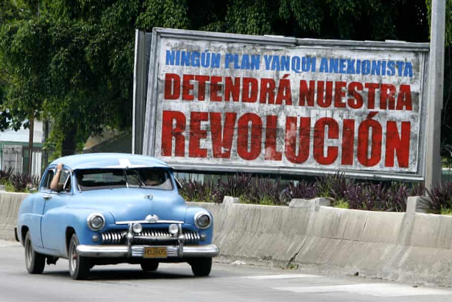 """An old American car drives past a billboard in Havana that reads """"No Yankee annexation will stop our Revolution""""."""