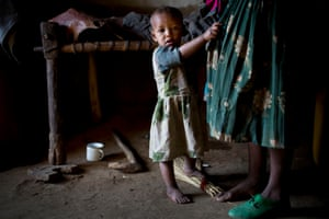 A young girl clings onto her mothers skirt in their home  in the village of Addis Ge, near Fiche, Ethiopia Saturday, Feb. 21, 2015.