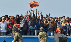 Royal Marines from HMS Bulwark help rescue migrants stranded on a boat, thirty miles off the Libyan coast, on 7 June.