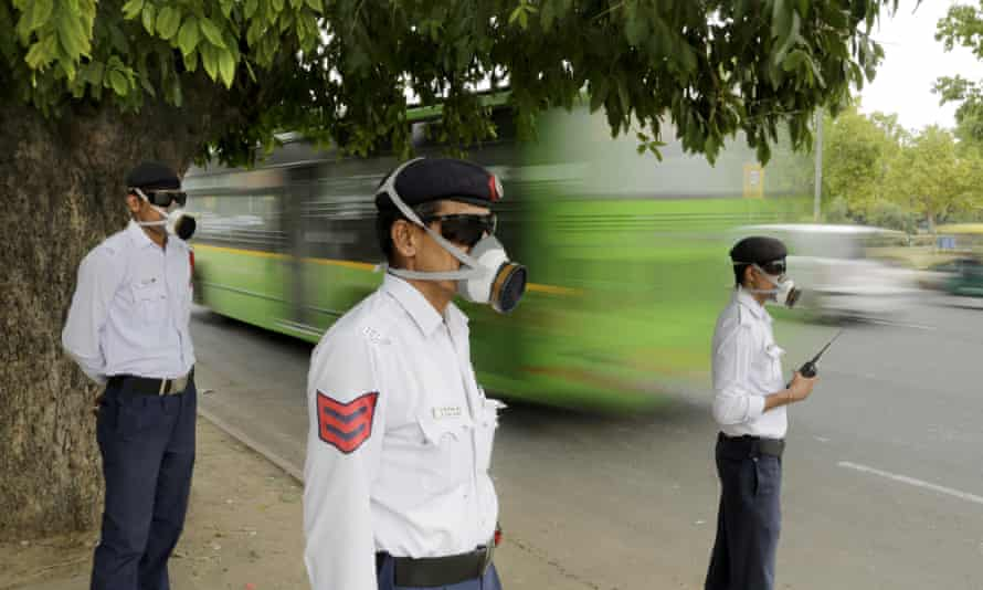 Police officers wear masks as they control traffic in Delhi.