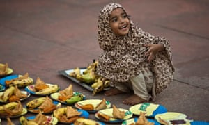 A girl arranges plates before iftar