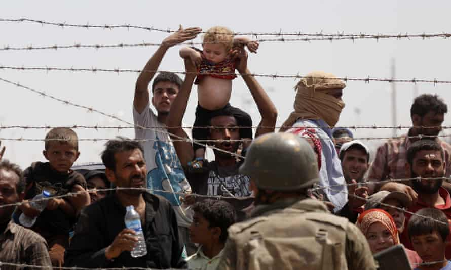Syrian refugees trying to cross the border into Turkey.