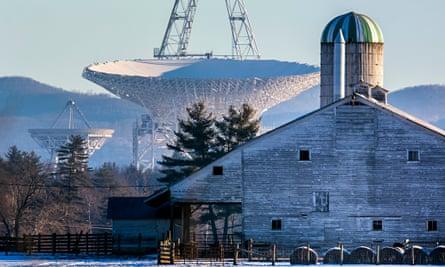 big telescope towering over wooden barn