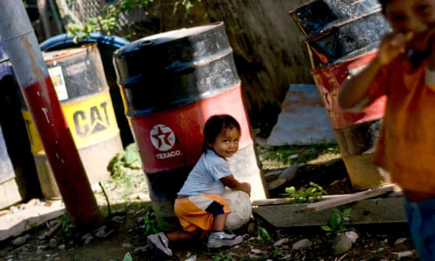 A child from the Huaorani tribe, also known as the Waos, who are native Amerindians from the Amazonian Region of Ecuador, plays near a discarded Texaco oil drum