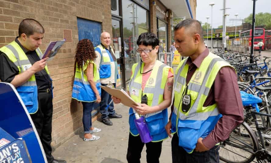 Supervisors Mohammed Haque (right) and Tracey Grant (2nd right) discuss  break times as fellow Business and Community Wardens wait in Finsbury Park, London on Friday, June 12, 2015.  The government's community work placement is intended to give long time unemployed people work experience. However, they say they are standing around for 30 hours a week and get no experience, cannot pay for food and receive no help with applying for jobs.Photograph:    Frantzesco Kangaris