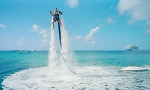 An employee of Jetpack Cayman is propelled up out of the sea by a motor pumping water into a jetpack