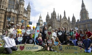 Climate change campaigners pose in front of the Houses of Parliament in London on June 17, 2015, ahead of mass lobby to urge members of parliament to back strong action on climate change.