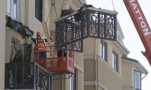 Workers remove part of a balcony that collapsed.