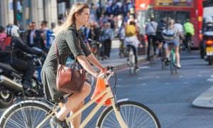 A woman riding a bike through London