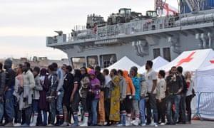 Migrants queue at the port of Catania