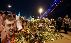 People walk past flowers at the site where Russian politician Boris Nemtsov was killed, with St. Basil's Cathedral seen in the background, 9 March 2015.
