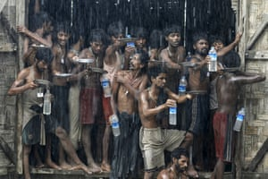 Migrants, who were found at sea on a boat, collect rainwater at a temporary refugee camp in northern Rakhine state, Burma, 4 June 2015.