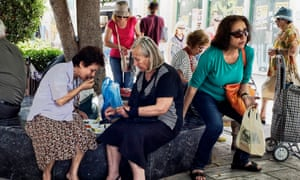 Pensioners eat a meal on streets of Athens.