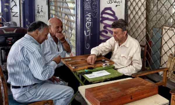 Pensioners play backgammon in front of closed shops in Athens, Greece.