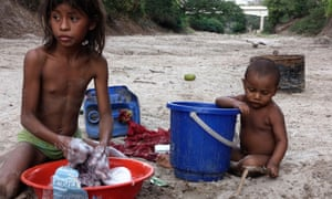 Esteffany Epieyu, 11, and her nephew Luis Miguel wash clothes in the dry riverbed.