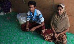 Rohingya woman Azima sits next to her husband, Hussein, at his family apartment in Bangkok, Thailand.