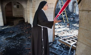 A nun inspects damage at the Church of the Multiplication at Tabgha.