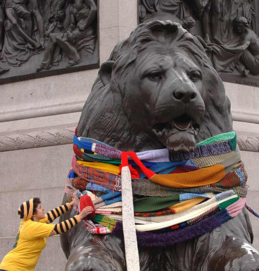 A member of the 'Stitch and Bitch' knitting group wraps giant colourful scarves around the Trafalger Square lions in London.