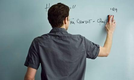 Teacher erasing whiteboard.