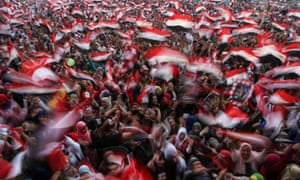 Egyptians wave national flags at a celebration in Cairo's Tahrir Square on 3 June 2014.