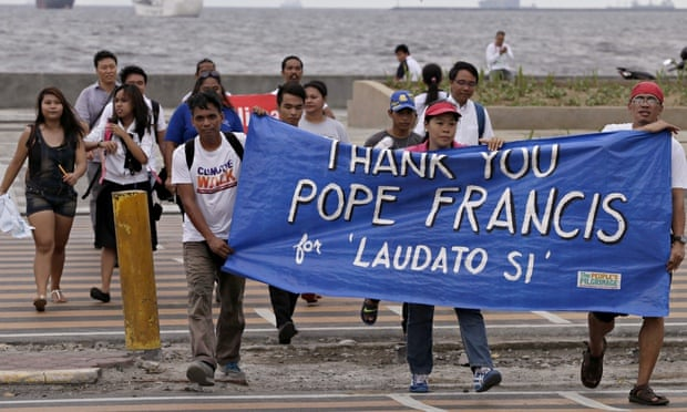 Environmental activists carry a banner thanking the pope