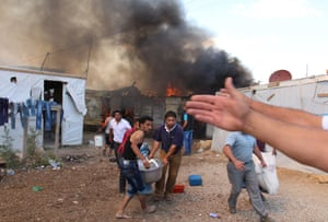 Syrian refugees carry away a machine as fire engulfs structures at an unofficial Syrian refugee camp in Lebanon's Bekaa Valley, on 1 June 2015, which killed a child and injured several others.
