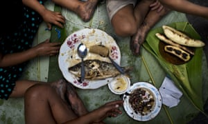 In this April 20, 2015 photo, siblings Piero, Ariana and Priscila eat a lunch of fish, bananas and rice as their parents sell fish at a street market in Belen, a neighborhood nicknamed  Venice of the Jungle  in Iquitos, Peru. According to official statistics, 40 percent of the children in Belen suffer from malnutrition and 66 percent of the entire population is poor.