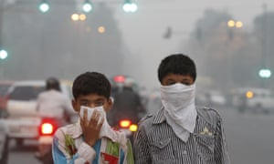 Children cover their faces to try to protect themselves from air pollution in the Indian capital.