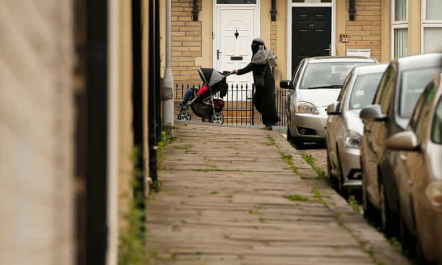 A woman pushes her pram along a street in east Bradford