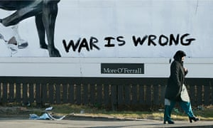 A Muslim woman walks by an advertising hoarding defaced with graffiti.