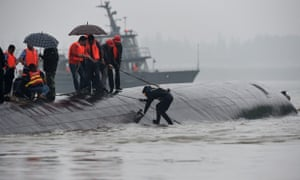 Rescuers work on the overturned passenger ship in the Jianli section of the Yangtze River.