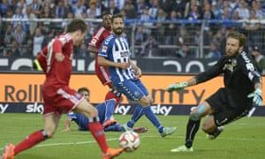 Hamburg's midfielder Nicolai Mueller scores the winning goal past Karlsruhe's goalkeeper Dirk Orlishausen during the relegation play-off second leg against Karlsruher SC.