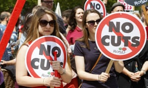 Protesters in Bristol carry anti-austerity placards .