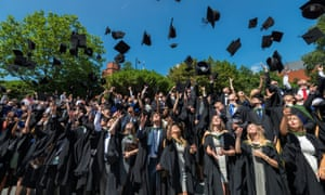 Graduates throw their mortarboards in the air