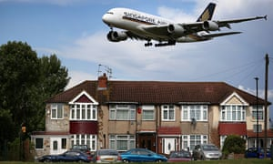 A passenger plane comes in low over housing as it lands at Heathrow airport.