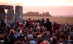 Crowds gather as dawn begins to break.