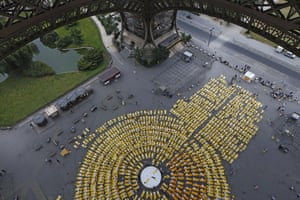 Hundreds of people attend a yoga session under the Eiffel Tower in Pari