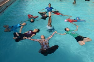 Indian children perform water yoga at a swimming pool in Jodhpur