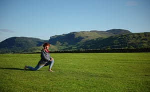 A woman practices yoga at Castlerigg stone circle on the evening of the Summer Solstice in Keswick, UK