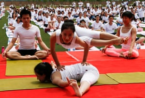 Instructors perform yoga poses for practitioners at Geely University in Beijing, China