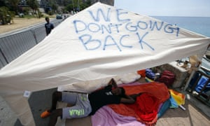 A migrant lies under a tent with the words 'We don't going back' written on it, Ventimiglia at the Italian-French border, where a group of migrants has been camping since being refused entry into France.