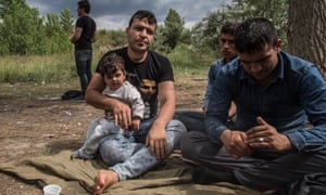 Yama Nayab with his daughter and other migrants in a makeshift camp in the fields and brush of an abandoned brick factory in the outskirts of Subotica, Serbia.