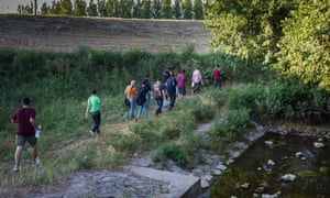 A group of Syrian migrants make their way through the woods hugging a river outside of Kanjiza, Serbia.